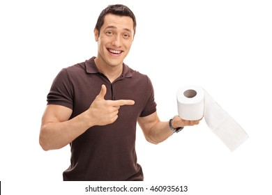 Joyful young man holding and pointing towards a roll of toilet paper isolated on white background