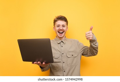 Joyful young man in shirt and glasses stands with laptop in hands on yellow background, looks into camera and shows thumb up. Portrait of happy nerd with laptop in hands. Isolated.