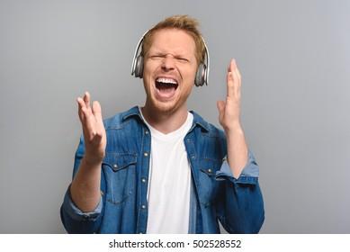 joyful young man singing in headphones