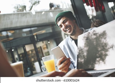 Joyful young man with a smartphone in his hand sits with his girlfriend who works for a laptop in a cafe next to a large window at lunchtime