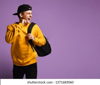 Joyful young man student with a backpack runs isolated in studio on a purple background.