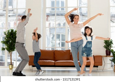 Joyful young mommy jumping with adorable daughter, happy father dancing with cute son to favorite energetic music tracks in living room at home. Joyful family enjoying dancing party in living room.