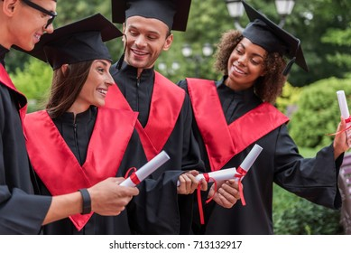 Joyful young students showing their diplomas in graduation clothing