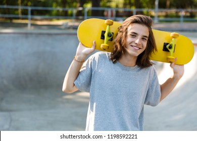Joyful young teenge boy spending time at the skate park, holding a skateboard