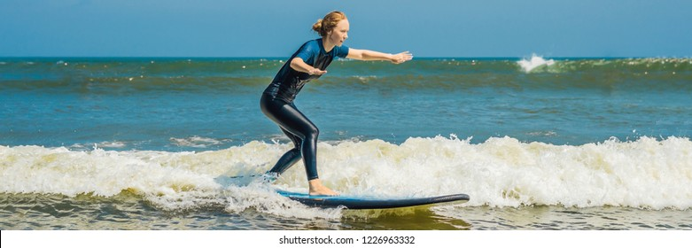 Joyful young woman beginner surfer with blue surf has fun on small sea waves. Active family lifestyle, people outdoor water sport lesson and swimming activity on surf camp summer vacation BANNER, LONG