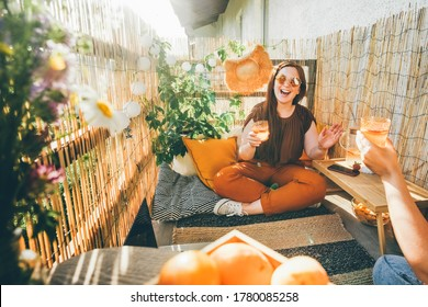 Joyful young woman clinks glasses with delicious cocktails with friend spending time together on decorated terrace on summer day close view.