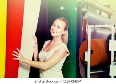 joyful young woman customer choosing bolt of fitted carpet in housewares hypermarket