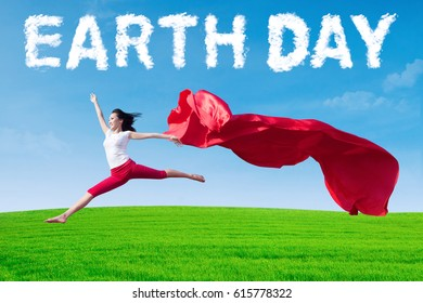 Joyful young woman dancing on the meadow while holding a red fabric with cloud shaped Earth Day text. Earth Day concept