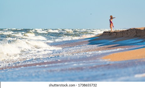 Joyful young woman enjoys stormy waves of the sea looking far beyond the horizon on a sunny summer day while relaxing on the sea. Concept of vacation and privacy. Copyspace