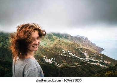 Joyful young woman with flying hair hidden her face looks at the camera in front of Taganana village on north of Tenerife. Concept of travelling, happiness, freedom. Canary Islands, Spain