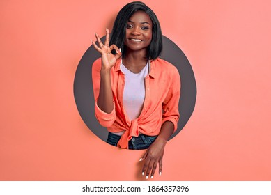 Joyful young  woman gesturing okay sign smiling in camera standing in circle hole in coral background in studio.