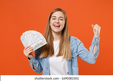 Joyful young woman girl in casual denim clothes posing isolated on orange background. People lifestyle concept. Mock up copy space. Hold fan of cash money in dollar banknotes, doing winner gesture