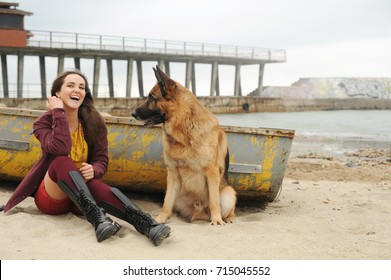 Joyful young woman have a rest with her German shepherd dog outdoor near old boat
