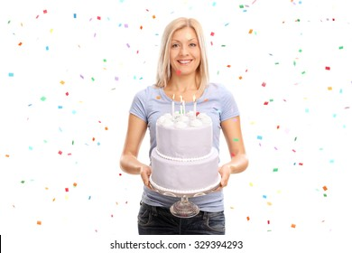 Joyful young woman holding a birthday cake and smiling with confetti streamers in the air all around her isolated on white background