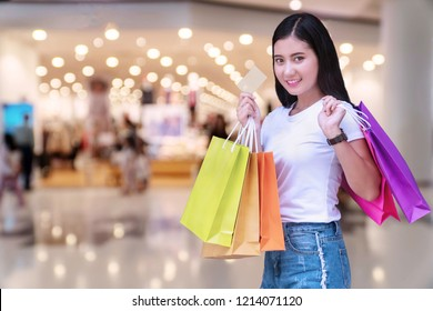 Joyful young woman holding shopping bags and blank credit card on Shopping malls background with copy space. Happiness, consumer, sale and people concept.