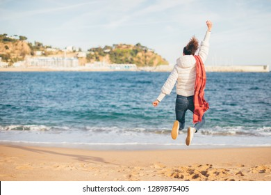 Joyful young woman jumping and celebrating on the beach (Costa Brava, Spain) - success, happiness, freedom and superwoman concept