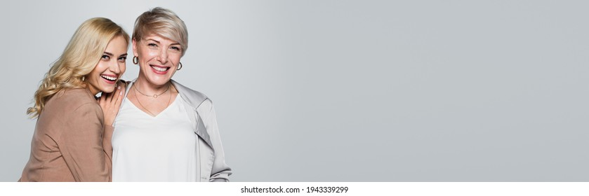 joyful young woman leaning on shoulder of stylish mother isolated on grey, banner