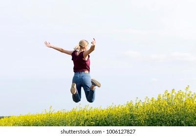joyful young  woman leaping in the rape field, rear view