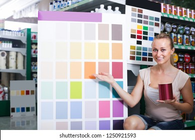 joyful young woman looking at color palette in housewares hypermarket