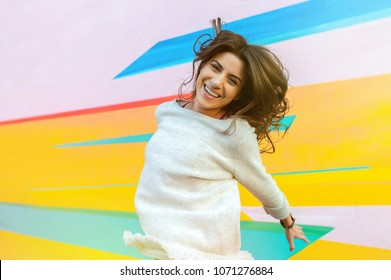 Joyful young woman on the street jumping on air looking happy and enjoying the time outdoor.