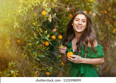 Joyful young woman, outdoors at sunset in a orange orchard, looking at camera and smiling, holding an orange fruit. Healthy lifestyle concept, skin and hair care concept.