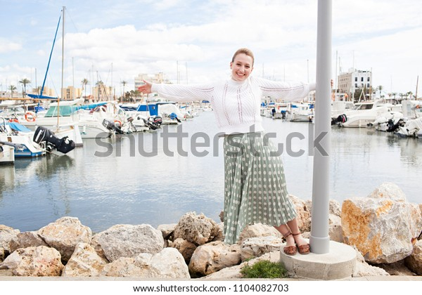 Joyful young woman playful hanging off lamp post on rocks in boats port in a coastal destination holiday, sunny outdoors. Fun female smiling, travel recreation adventure discovery leisure lifestyle.