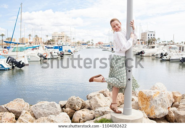 Joyful young woman playful hugging lamp post in fishing boats port in a coastal destination holiday, sunny outdoors. Fun female smiling, travel recreation adventure discovery leisure lifestyle.