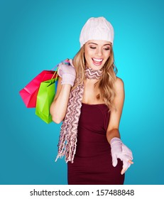 Joyful young woman with shopping bags wearing a trendy cap, scarf, and gloves laughing as she dangles the brightly coloured bags over her shoulder, over blue