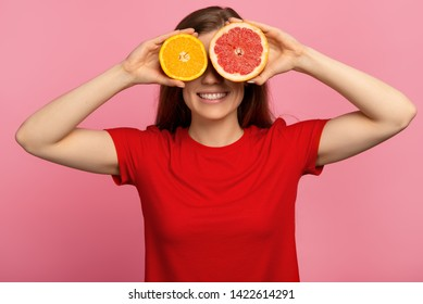 Joyful young woman smiling teeth on her face and holding an orange and grapefruit near the eyes, isolated on a pink background