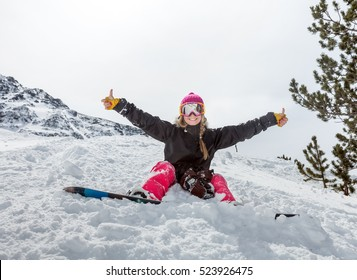 Joyful young woman snowboarder sitting in the snow wearing a mask shows a sign on the background of beautiful mountains