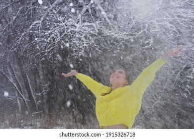 Joyful young woman throws handful of fresh powder snow high into  air on winter day. Lady in bright yellow sweater in frosty forest for walk.