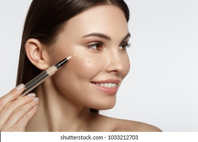 Joyful young woman using concealer and smiling. She is holding special brush near her face. Drops of foundation are on cheek. Isolated and copy space
