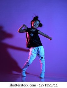 Joyfull asian kid girl in shirt and pants with stars on purple background dances with closed eyes like a disco star