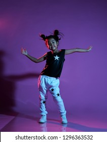 Joyfull asian kid girl in shirt and pants with stars and white sneakers on purple background dance