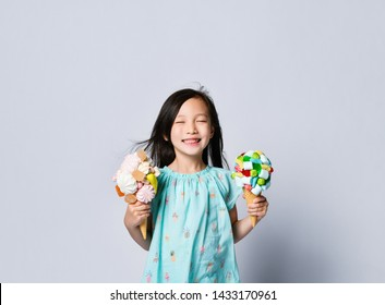 Joyfull funny asian baby girl holds close to her a couple of big ice-creams in waffles cones with berries marshmallow jelly beans on background with free text copy space above her