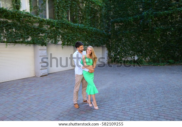 Joyfull sweet boy and girl, standing in full length posing for photo, smiling and embracing, guy looks at girl and stand in patio on background of house overgrown with vines and leaves outdoors. Girl