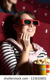 Joyfull woman is watching a movie at the cinema