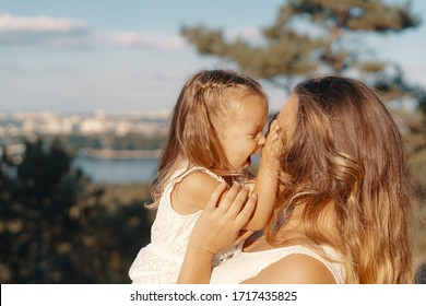 Joyfull young mother spend wonderful holiday time in the forest with her kid. Two blondies, mother and daughter