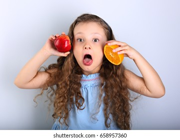 Joying humor grimacing happy kid girl with curly hair style holding citrus orange fruit and red apple in the hands and sticking the tongue out with surprising big eyes on blue background