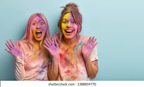 Joyous best female friends laugh and have fun together, show palms, smeared with colorful powder, celebrate Holi festival of colors, being in high spirit, giggle at funny joke, isolated on blue wall