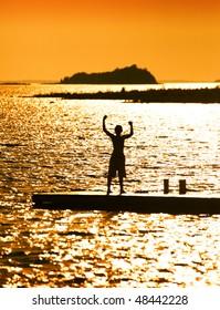 Joyous Boy Standing On Dock On Beautiful Afternoon