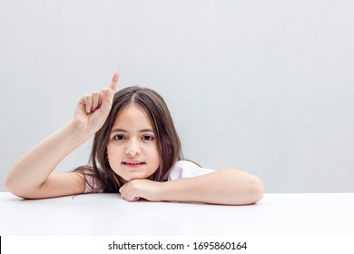 joyous cheeky child enjoying raising his fingers for fun school answers, expressing playful imagination and reflection, grey background