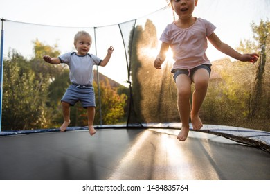 Joyous children jumping on trampoline in backyard