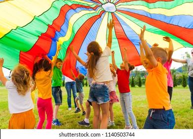 Freuen sich glückliche Klassenkameraden, die unter einem bunten Fallschirm springen