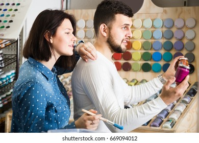 joyous couple examining various paints in paint supplies store