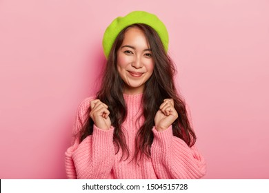 Joyous dark haired woman with pleasant smile, raises clenched fists, awaits something awesome, dressed in oversized sweater and beret, has natural beauty, isolated over pink studio background.