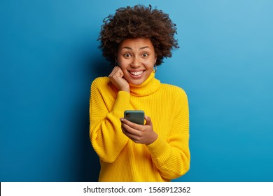 Joyous dark skinned young lady poses with mobile phone device, types text message on modern smartphone, watches funny video during free time, enjoys good internet connection, wears yellow sweater