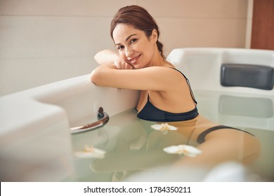 Joyous dark-haired lovely Caucasian young lady with a happy smile reclining in a hydromassage bath