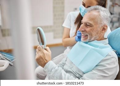 Freudender älterer Mann sitzt in einem Zahnstuhl mit einem Arzt an der Seite, während er in den Spiegel schaut