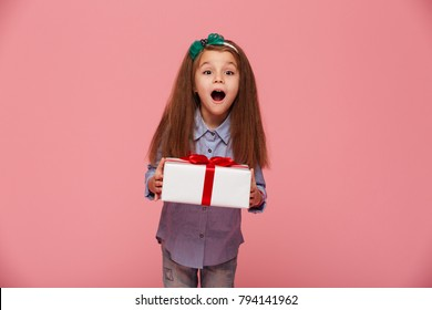 Joyous female kid shouting holding gift-wrapped box being excited and surprised to get birthday present, over pink background
